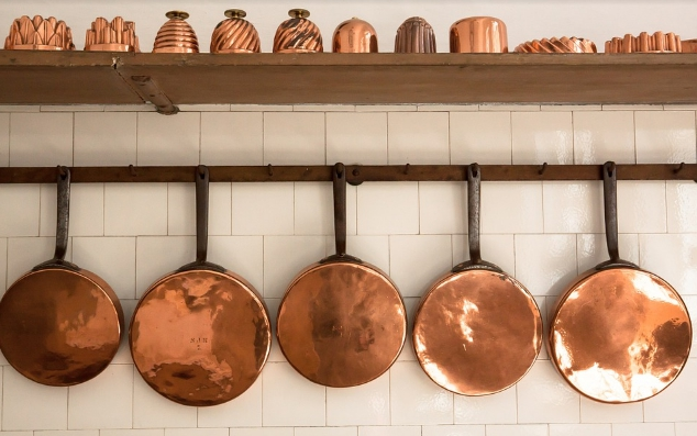 antique copper pots on wall